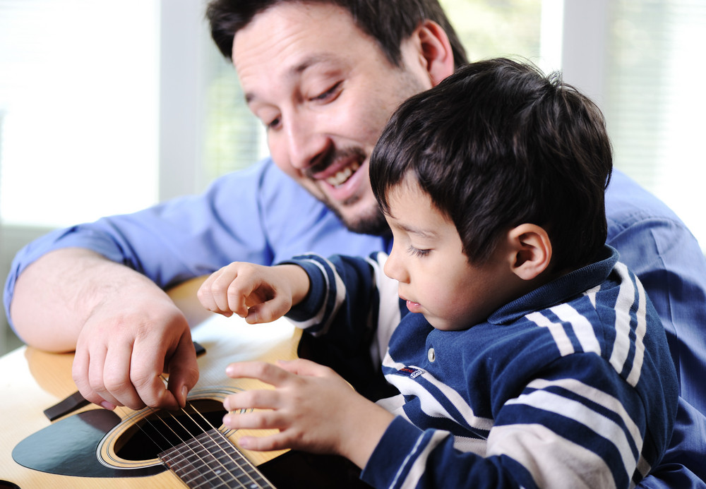 Father and son playing guitar at home Royalty-Free Stock