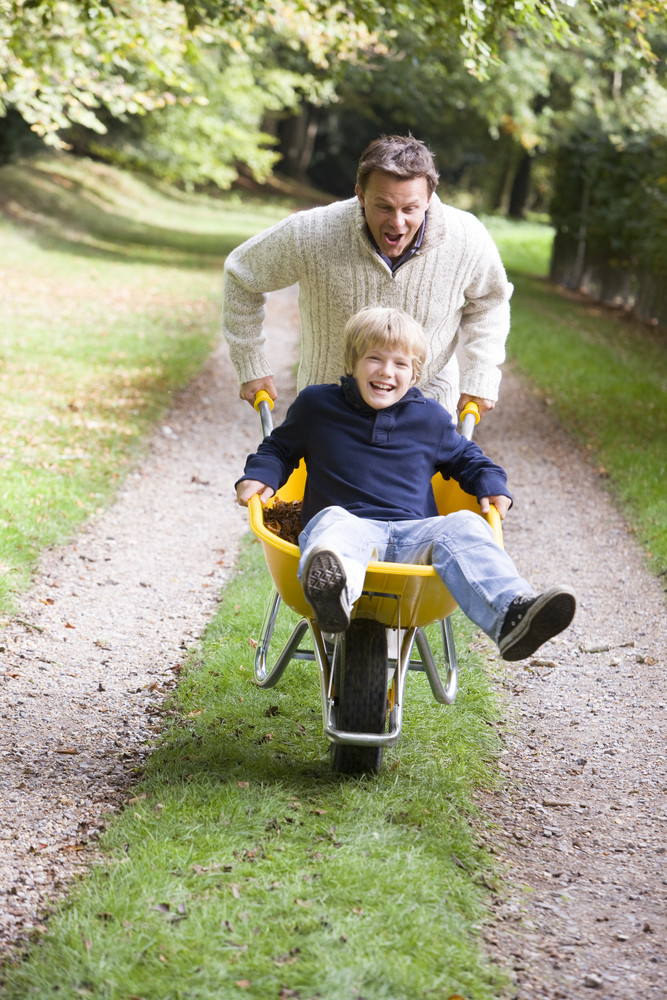 Father giving son ride in wheelbarrow through autumn woods