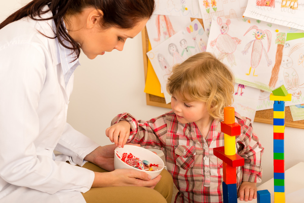 Female pediatrician offering lolly to child reward for bravery