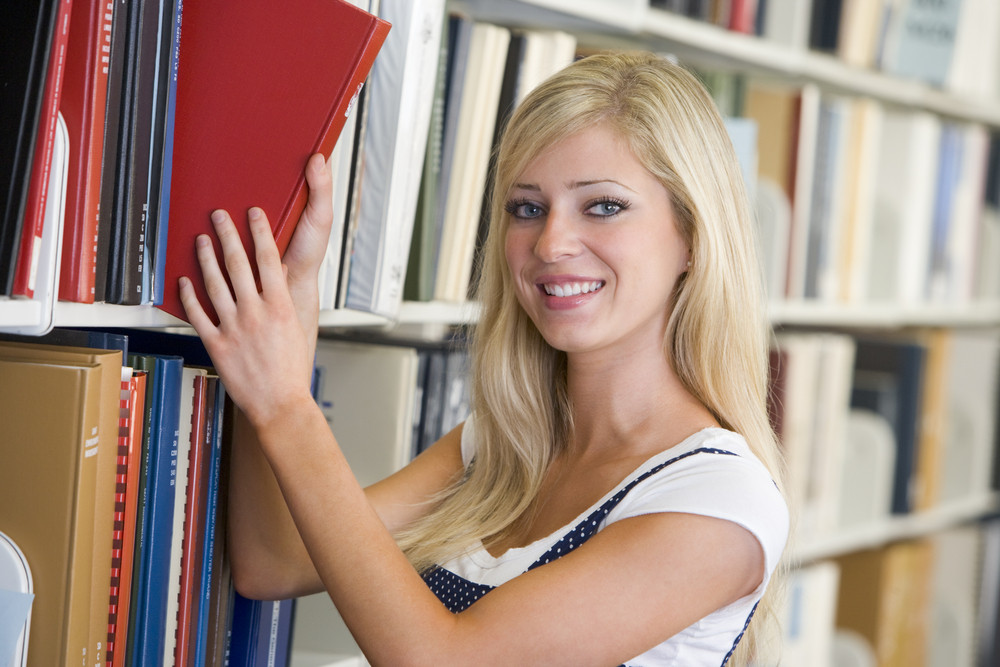 Female student selecting book from library shelf