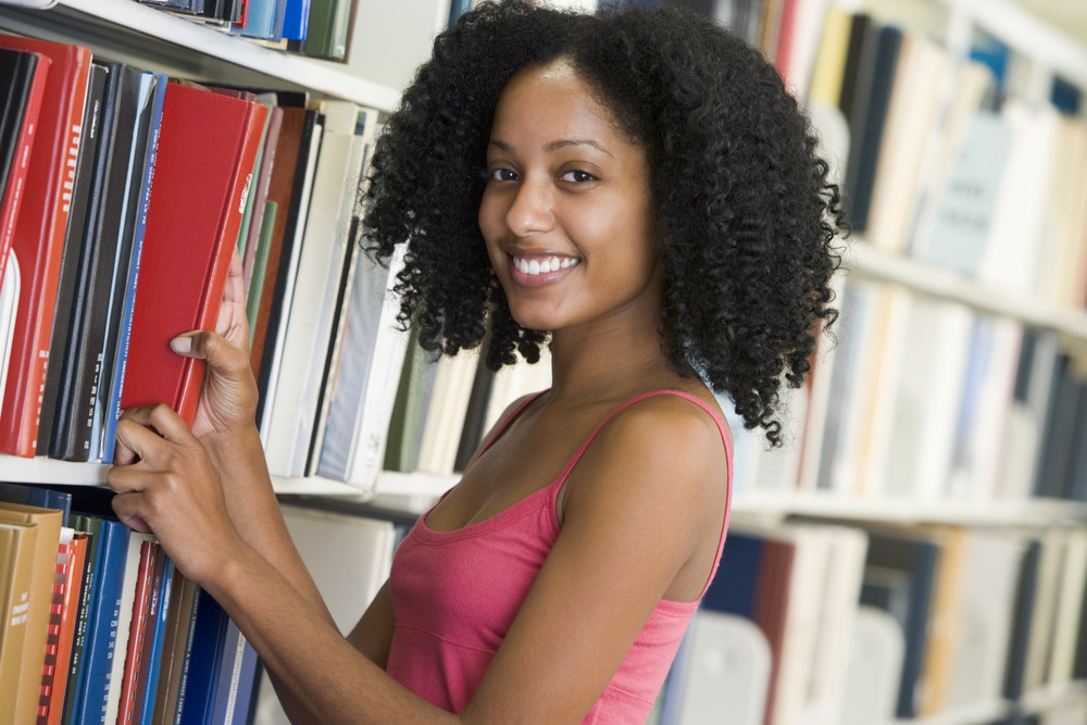 Female university student selecting book from library shelf