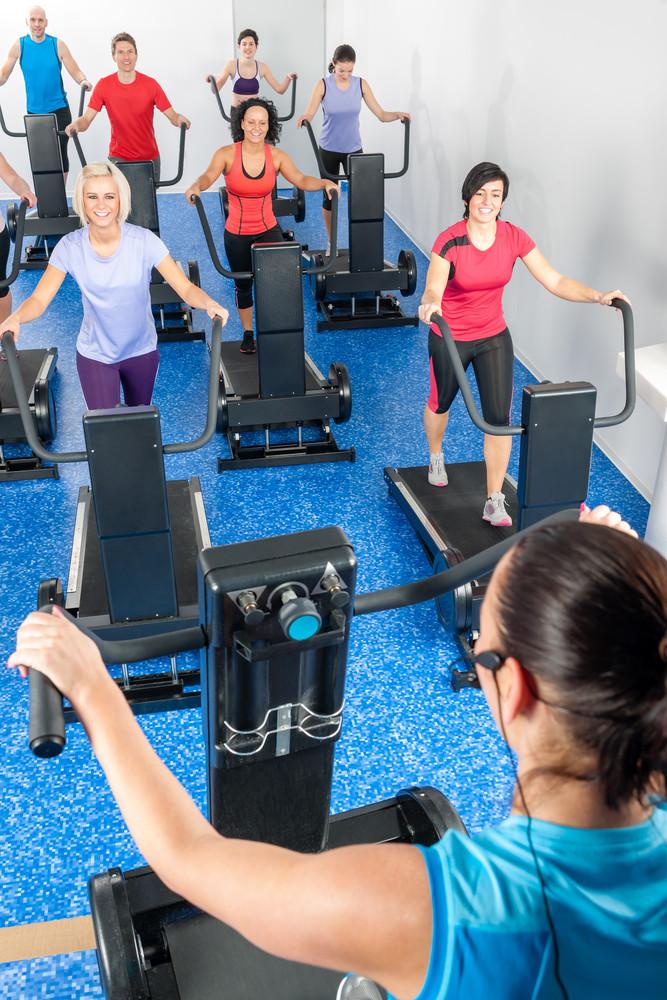 Fitness instructor leading treadmill running class at health club
