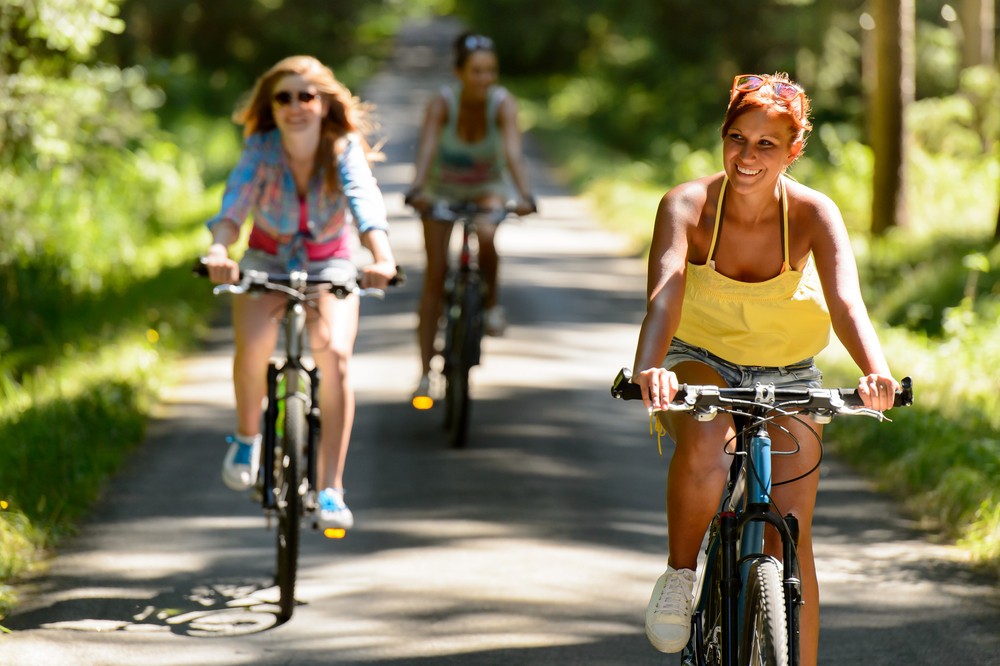 Friends riding their bikes in sunny countryside enjoy sport