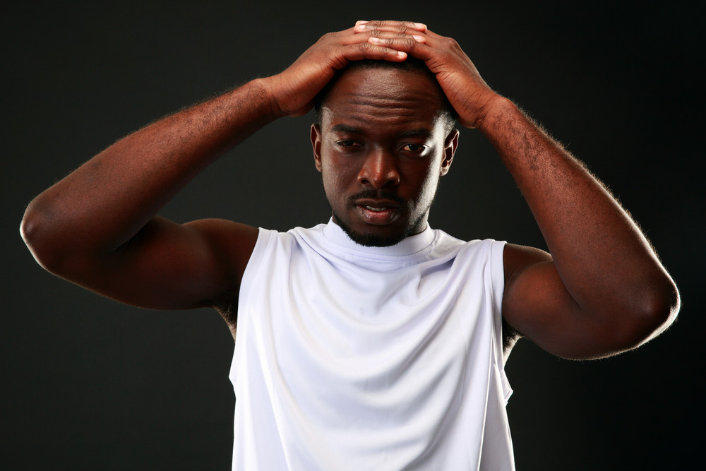 Frustrated african man touching his head over black background