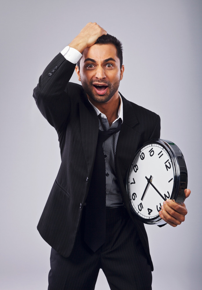 Frustrated businessman holding a clock