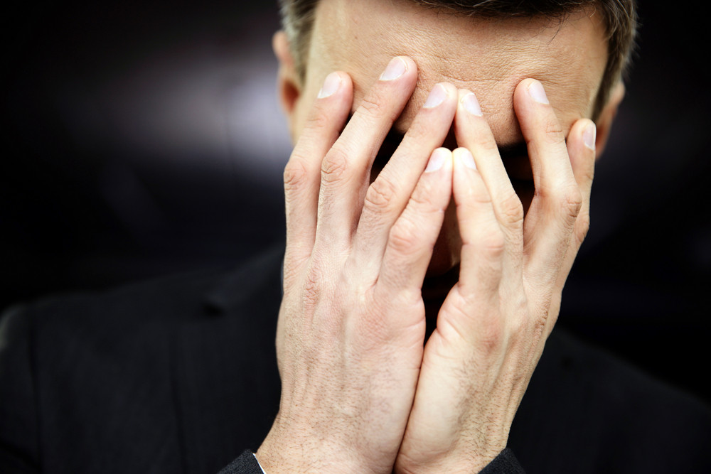 Frustrated man with hands on face
