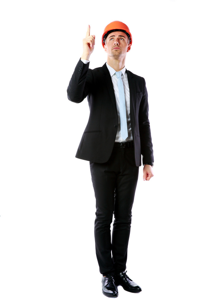 Full-length portrait of a businessman in helmet pointing up at copyspace over white background