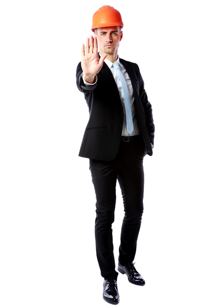 Full-length portrait of a businessman in helmet showing stop gesture over white background