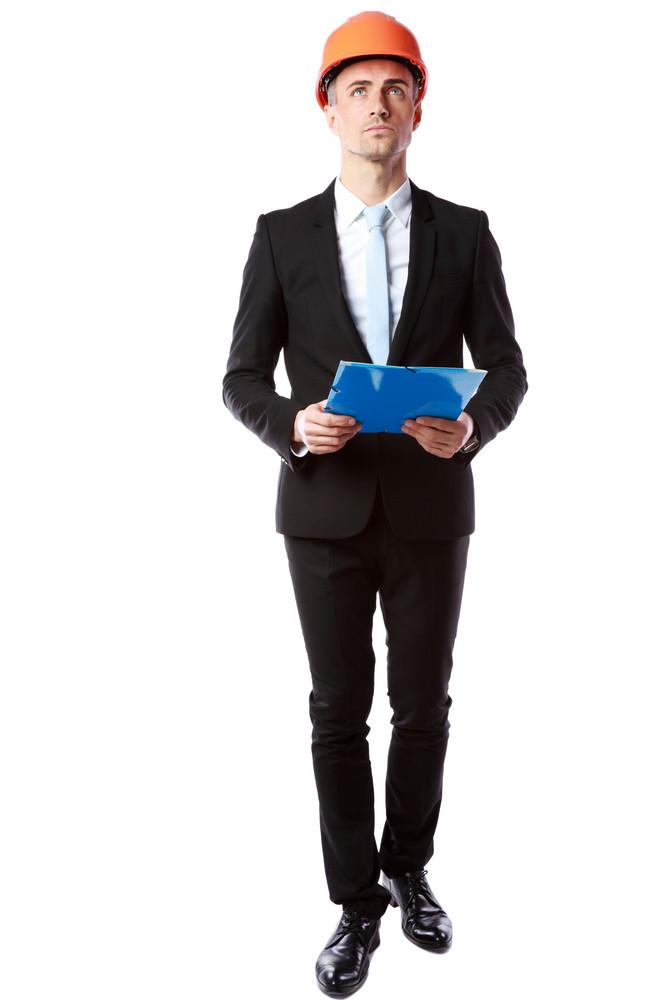 Full length portrait of a confident businessman in helmet holding blue folder over white background
