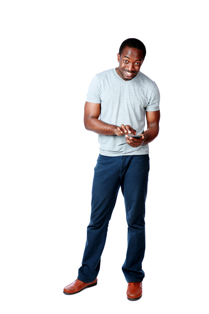 Full length portrait of a happy african man using smartphone over white background