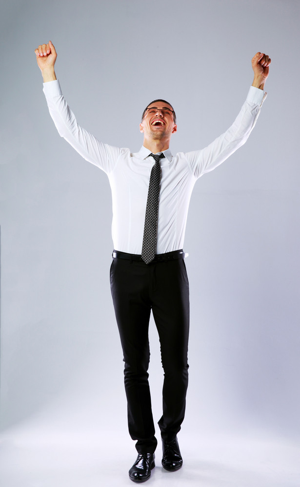 Full-length portrait of a happy businessman with hands raised up on gray background