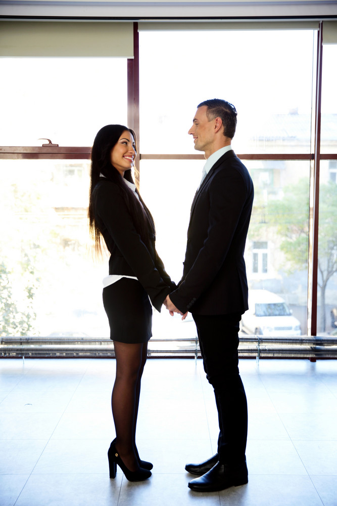 Full length portrait of a happy couple in formal cloth standing in office