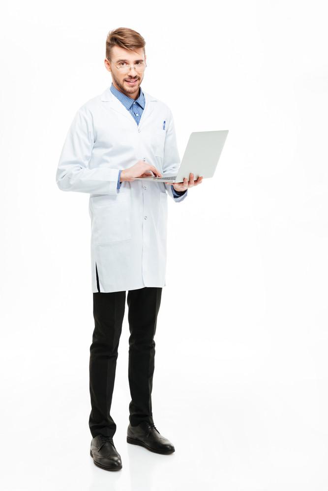 카메라를 보면 전체 길이 남성 의사 노트북 컴퓨터를 들고의 초상화 흰색 배경에 고립