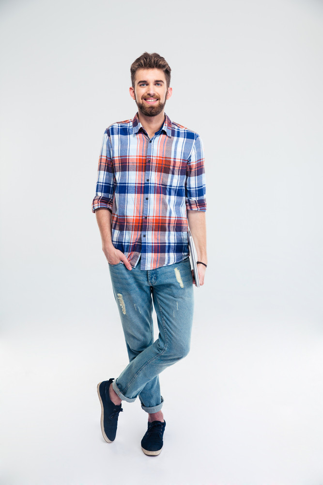 Full length portrait of a man standing with laptop