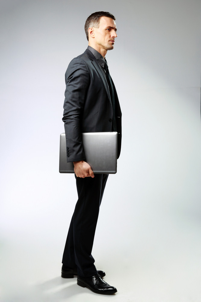 Full-length portrait of a pensive businessman standing with laptop on gray background