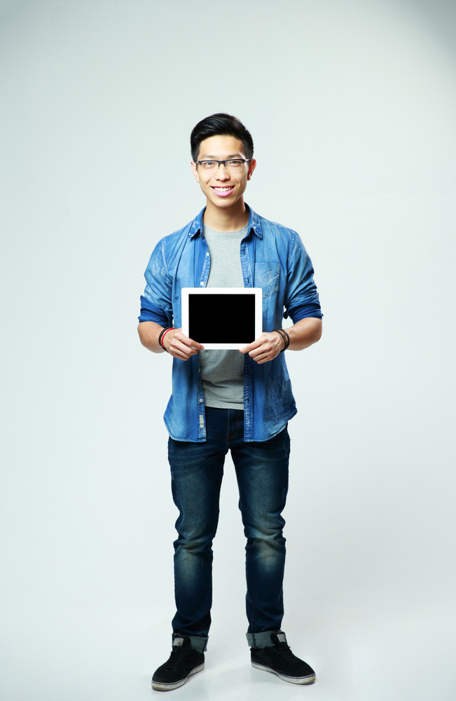 Full length portrait of a smiling man showing tablet computer screen on gray background