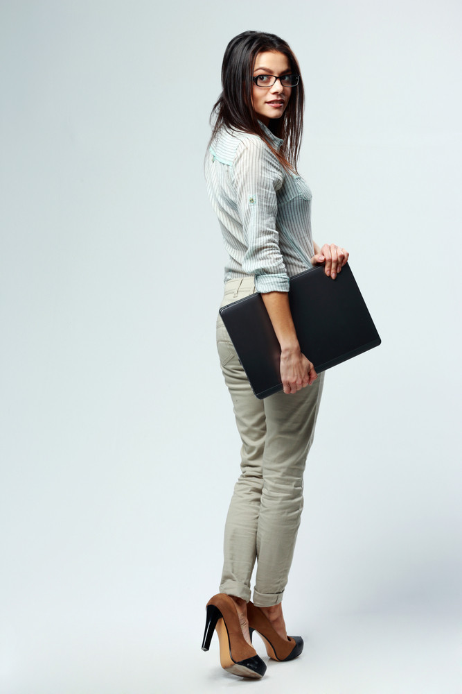 Full-length portrait of a young beautiful businesswoman holding laptop on gray background