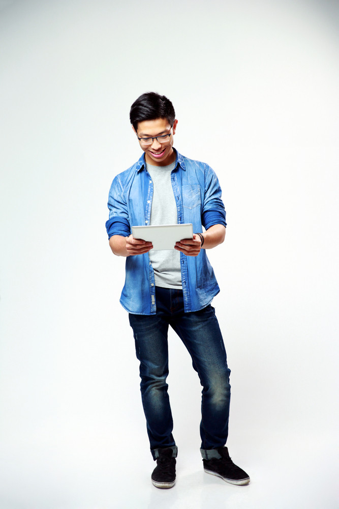 Full length portrait of a young happy man standing with laptop on gray background