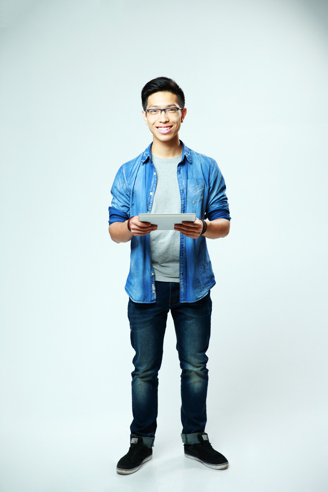 Full length portrait of a young smiling man standing with laptop on gray background
