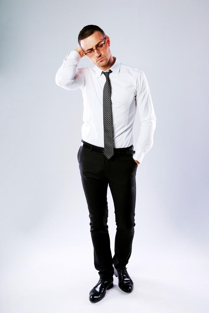 Full-length portrait of confident businessman on gray background