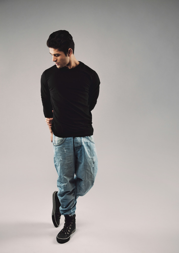 Full length portrait of hispanic young man in casuals posing. Male model looking down while standing on grey background.