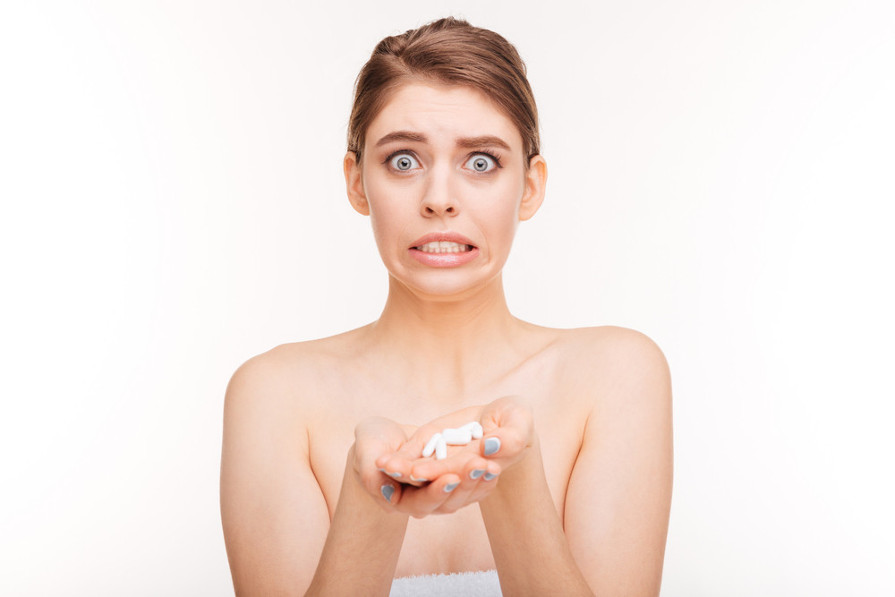 Funny woman holding pills isolated on a white bakground