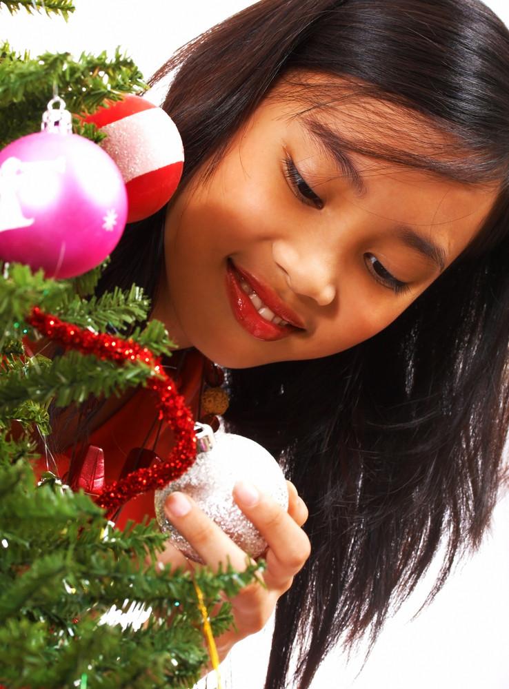 Girl Adding Balls To A Christmas Tree