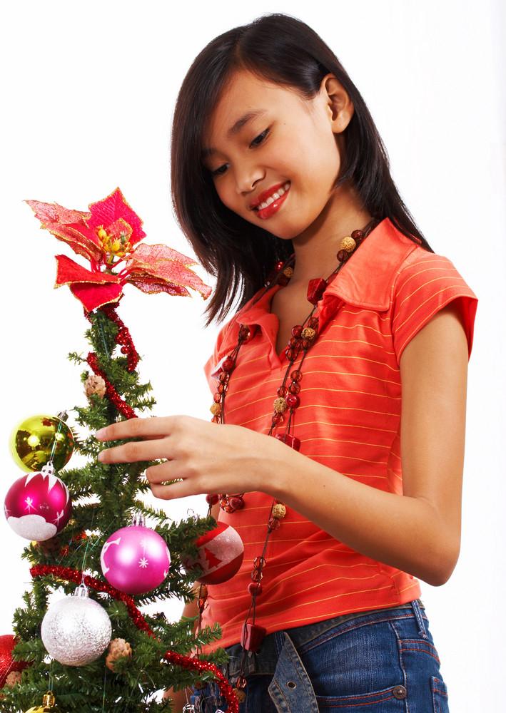 Girl Adding Tinsel To A Christmas Tree