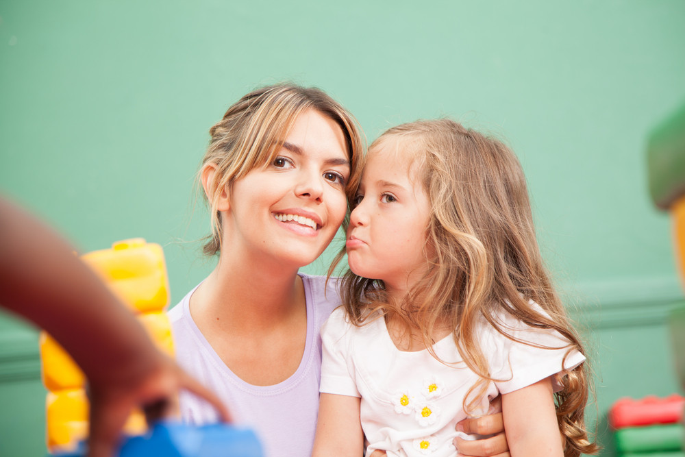 Girl and teacher playing in kindergarten