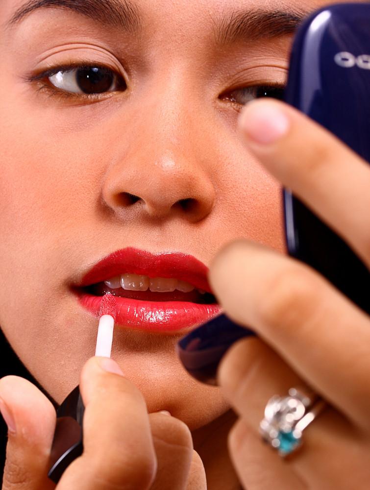 Girl Applying Lip Gloss Using A Mirror