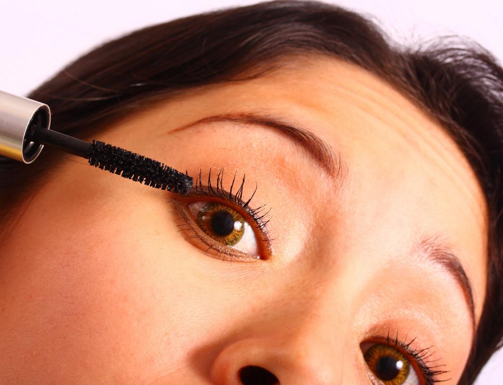 Girl Applying Mascara To Her Eyelashes