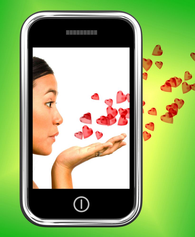 Girl Blowing Hearts From A Mobile Phone