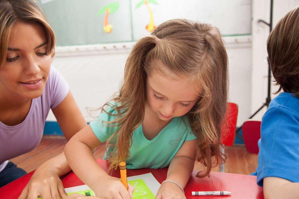 Girl drawing with her teacher
