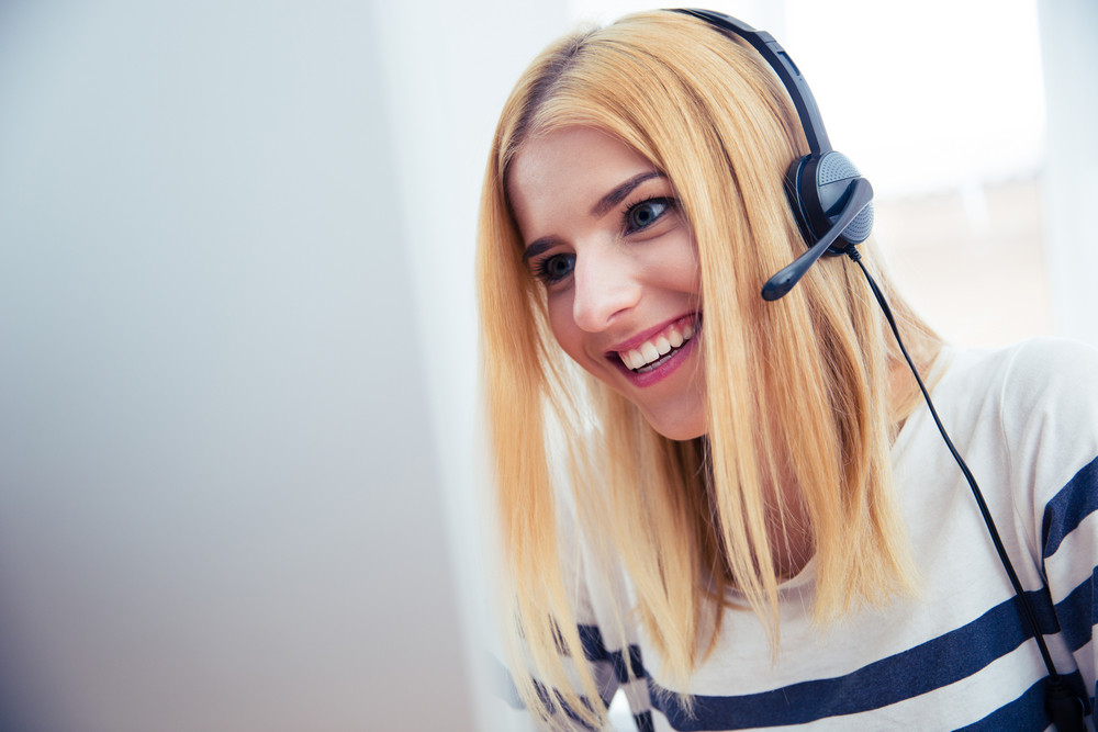 Girl in headset using desktop computer