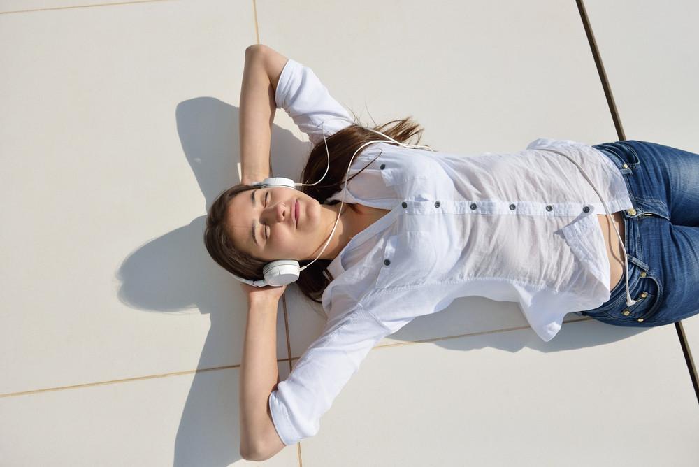 Girl listening to the music on white headphones