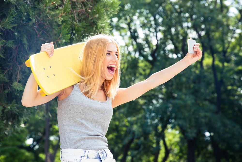 Girl with skateboard making selfie photo on smartphon