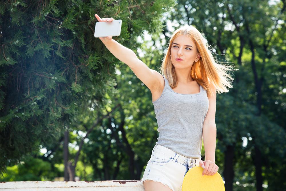 Girl with skateboard making selfie photo on smartphone
