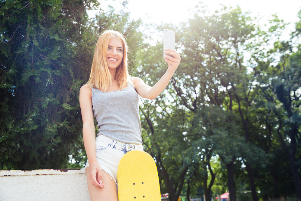 Girl with skateboard making selfie photo