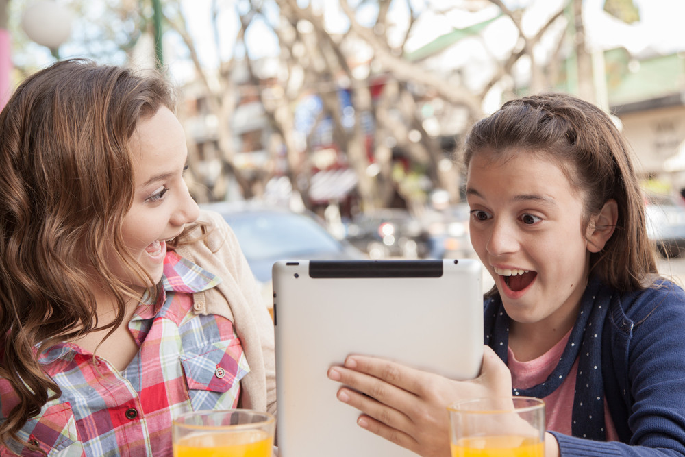 Girls using the tablet in the street