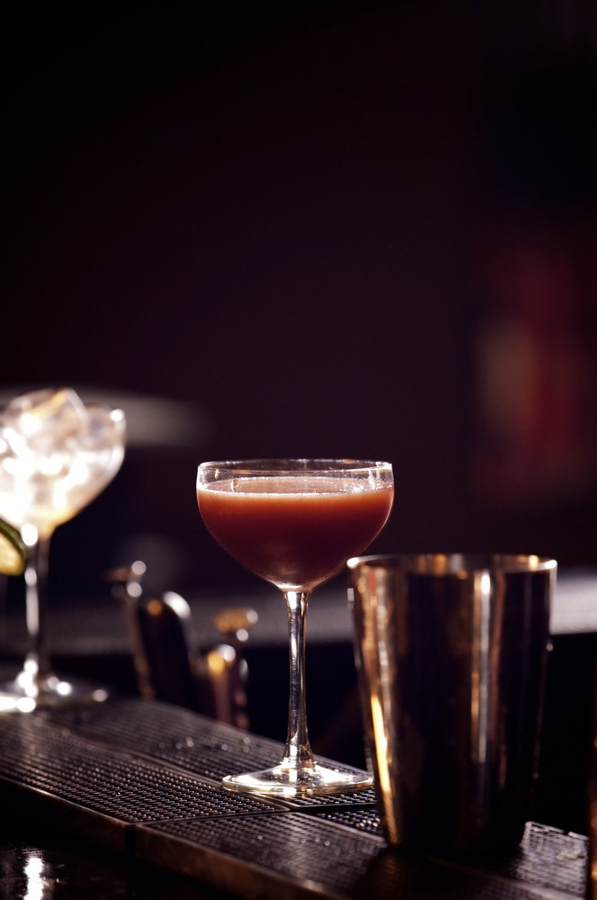 Glass of red wine with shaker on dark background