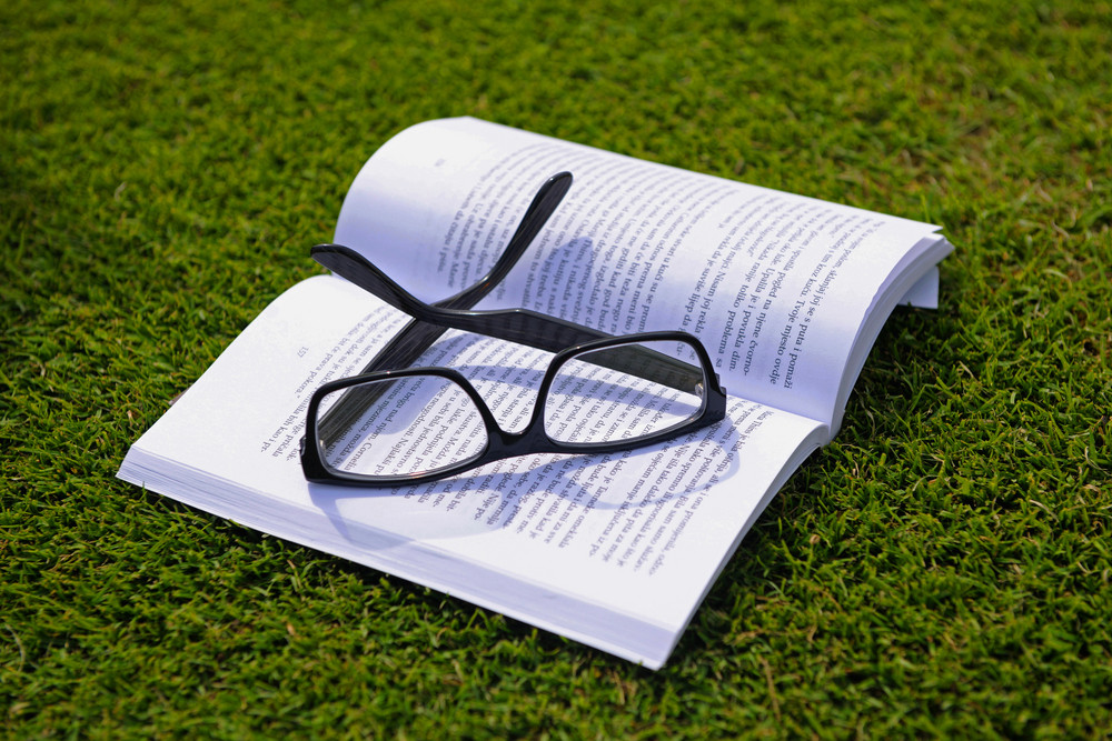 Glasses On A Book Outside With Grass In Background