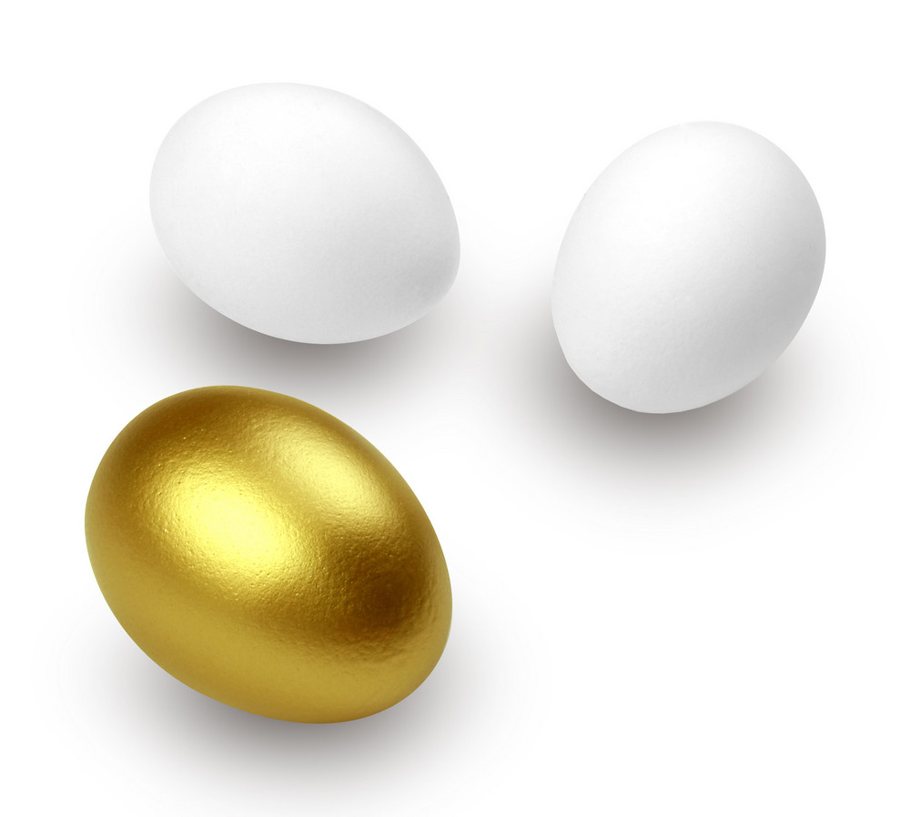 Golden Egg And Just Eggs Isolated On White