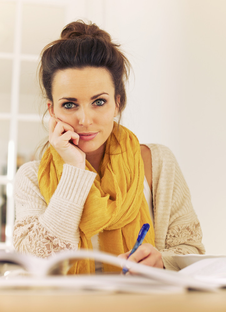 Gorgeous college girl writing something in her notes while in library looking at you