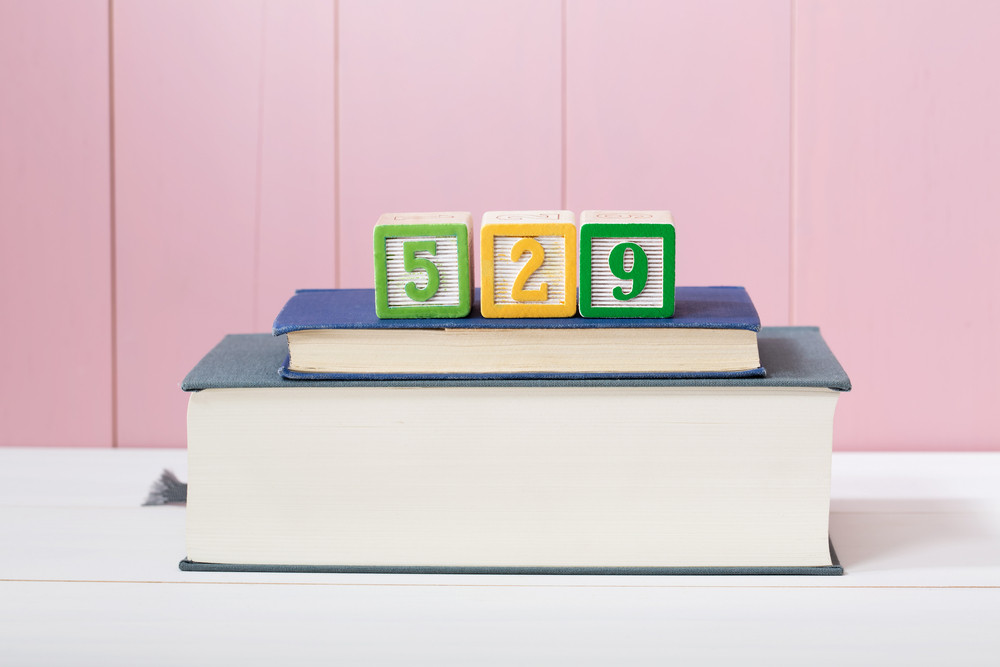 529 college savings plan concept with textbooks stacked in front of a pink wooden background with copyspace
