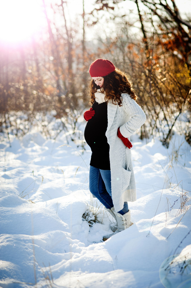 A beautiful pregnant woman is playing outside in the snow