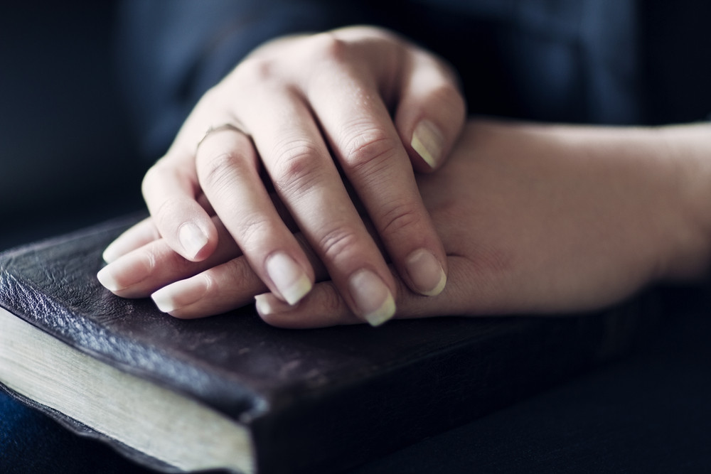 A close-up of a christian woman holding / reading the bible. Very shallow depth of fields. Toned.