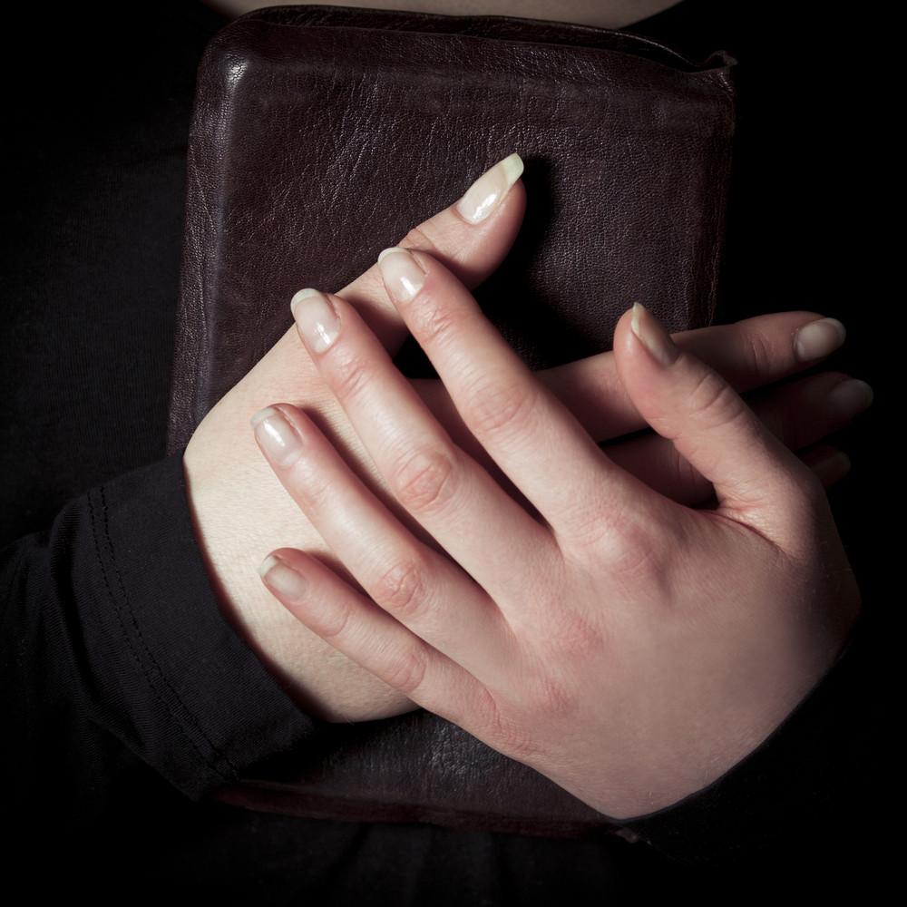 dc43954da A close-up of a christian woman pray. Holding a Cross over a bible ...