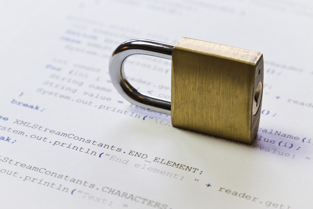 A padlock on Java program code. Symbol of software / application and computer security. High key photo. Can be used as background.