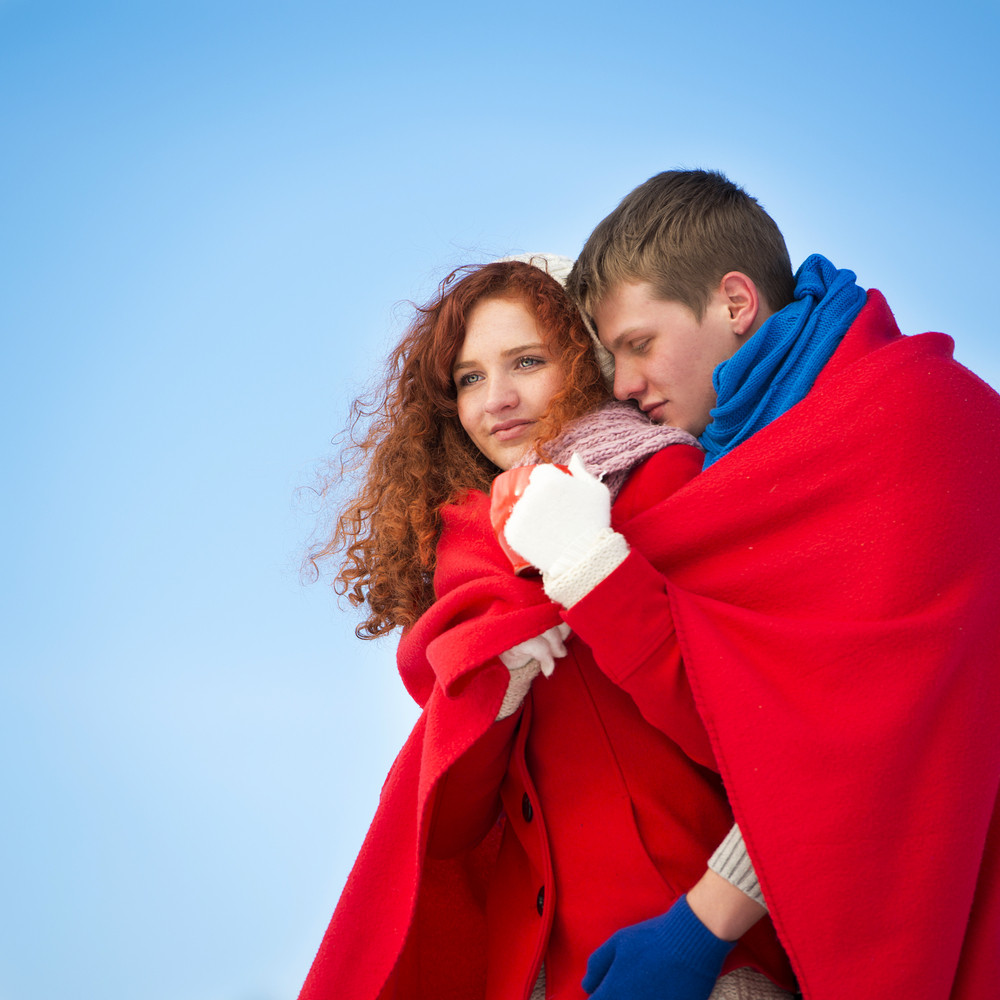 A romantic couple is warming up under the blanket outdoors