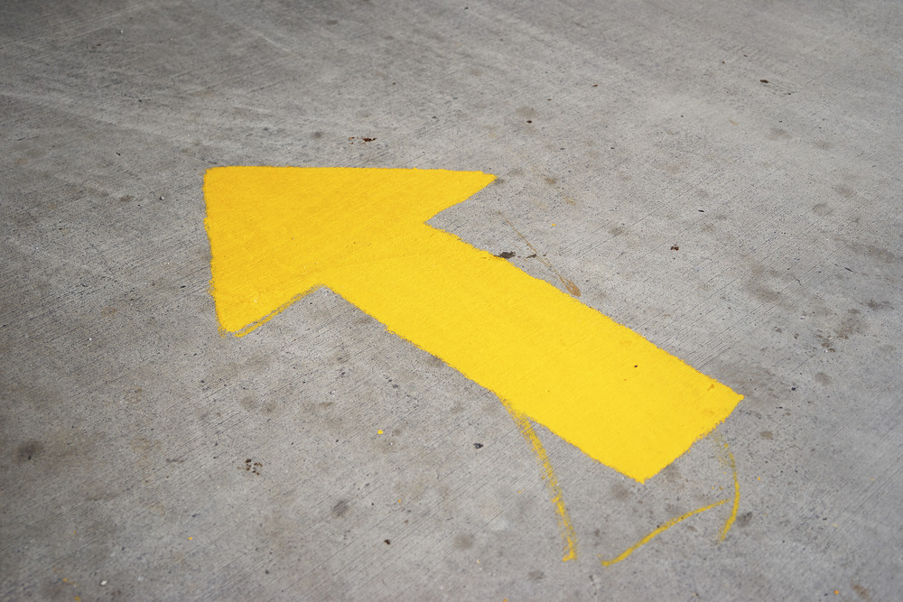 A yellow arrow symbol painted on a grungy concrete pavement.